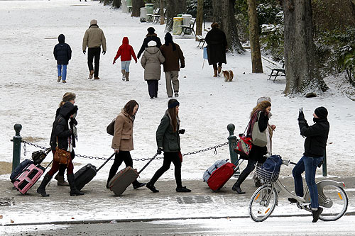 Tourists pull their bags over freshly-fallen snow in Paris as sub-freezing winter temperatures continue in Europe.