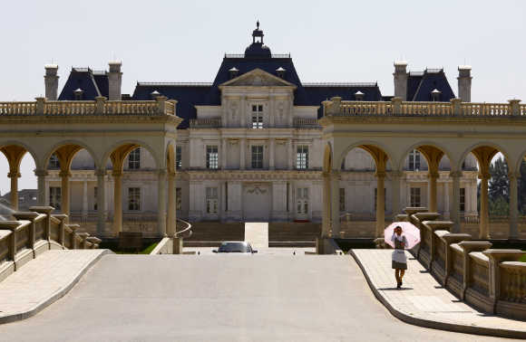 A waitress walks down the driveway to Chateau Laffitte Hotel located on the outskirts of Beijing.