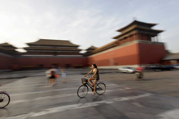 A foreign visitor rides a bicycle past Wumen Gate at the Forbidden City in Beijing.