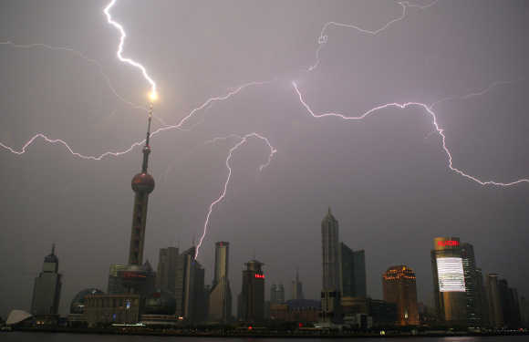 Bolt of lightning strikes Oriental Pearl Tower as others light up skyline above Pudong financial district in Shanghai.