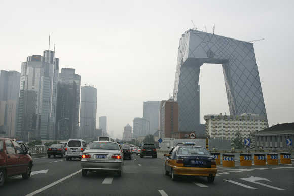 Vehicles pass a major thoroughfare towards the China Central Television headquarters, right, in Beijing.