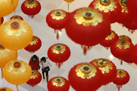People walk under lanterns at a shopping mall in Shanghai.