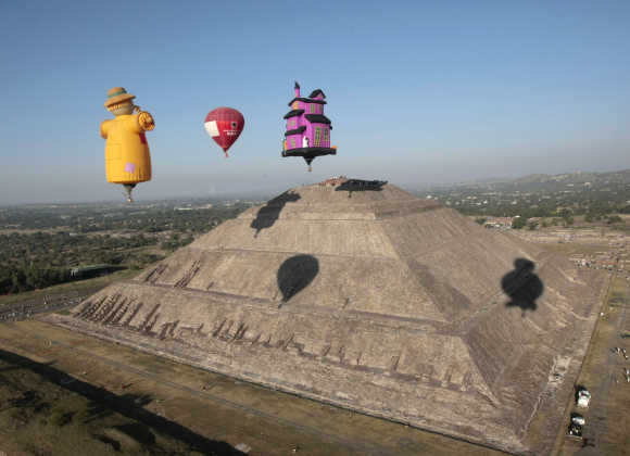 A hot air balloon floats past people watching the sunrise at the Sun pyramids of Teotihuacan outside Mexico City.
