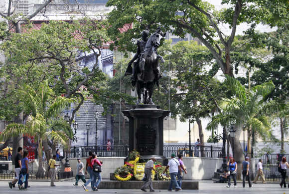 Poeple walk next to the statue of national hero Simon Bolivar at central Plaza Bolivar square in Caracas.