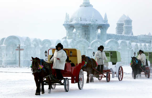 Horse-drawn carriages pass in front of ice sculptures at the 12th Harbin Ice and Snow World display in Harbin, Heilongjiang province, China.