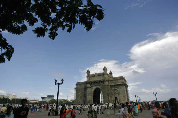 People stroll along the seafront near the Gateway of India in Mumbai.