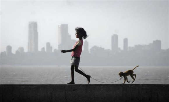 A girl walks with her pet monkey on a promenade along the Arabian Sea in Mumbai.