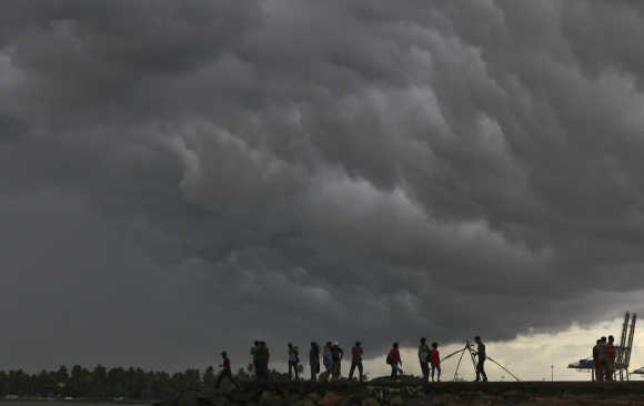 People stand on a seaside promenade against the background of pre-monsoon clouds gathered over the Arabian Sea at Kochi in Kerala.