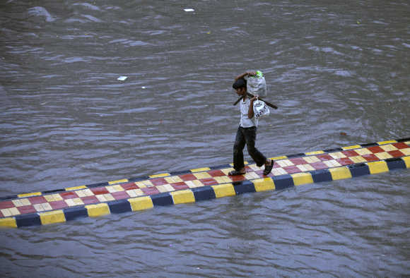 A man walks on a divider on a flooded road during heavy rain in Ahmedabad. A file photo.