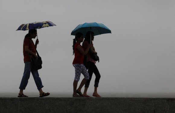 Girls walk on a seaside promenade as it rains in Mumbai. A file photo.