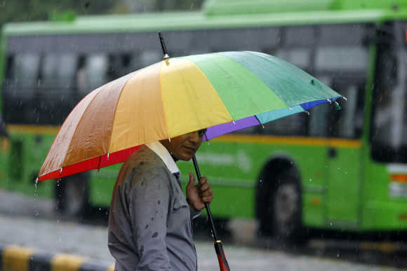 A man holds his umbrella as he crosses a road during rains in New Delhi. A file photo.