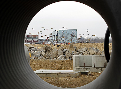 Seen through a water pipe, birds fly across a construction site where new multi-unit buildings are going up in Alexandria, Virginia.
