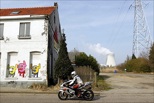 A motorcyclist rides past an abandoned house near the Doel nuclear plant.