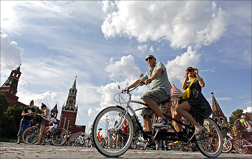 People cycle by the Kremlin as they take part in the Let's bike it! bike ride in central Moscow.