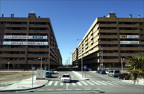 A car drives down the street near almost empty apartment blocks in the Madrid satellite town of Sesena.