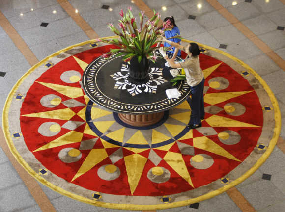 Workers display a flower arrangement on a table at a hotel in Hanoi.