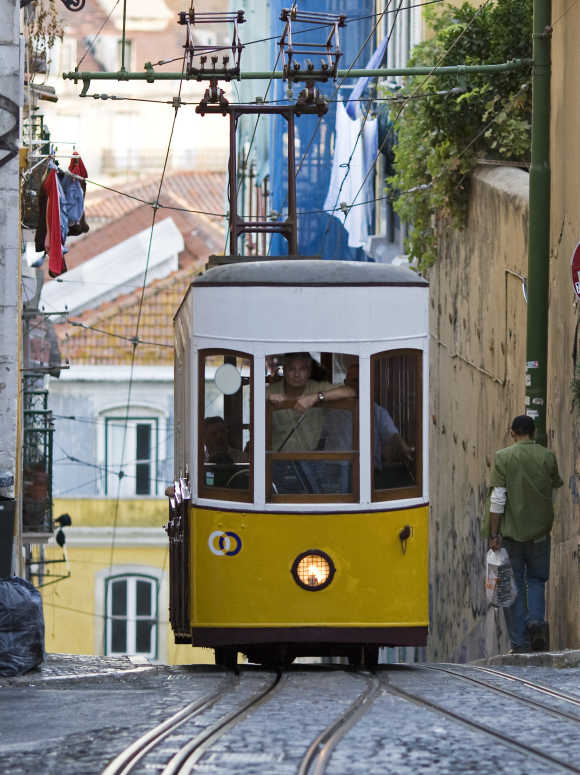 An employee looks through the open windscreen of Lisbon's Bica funicular. Different in shapes but serving one function - simplifying access to the upper town in the hilly Portuguese capital - Lisbon's street elevators are national monuments.