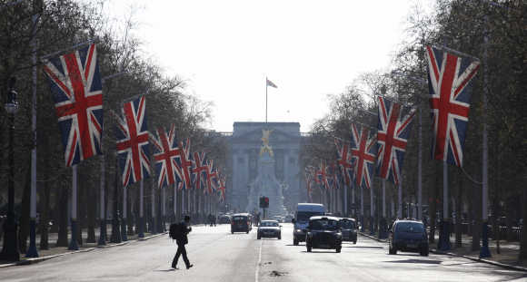 A man crosses the Mall, decked out in Union flags and with Buckingham Palace in the background, in London.