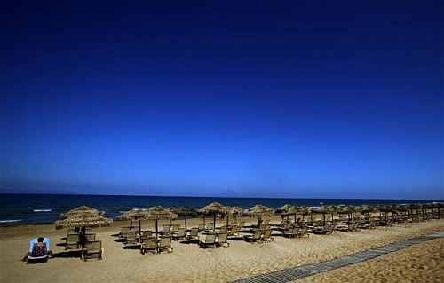 A tourist sits on a sunbed on the beach of the Olympia Riviera resort in the town of Killini, some 285 kms southwest of Athens