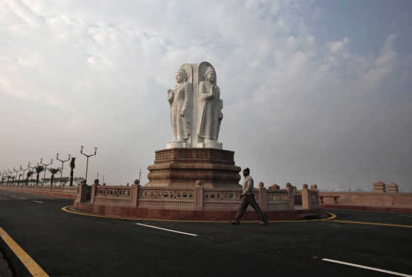 A man walks in front of Buddha statues outside the Ambedkar memorial park in Lucknow.