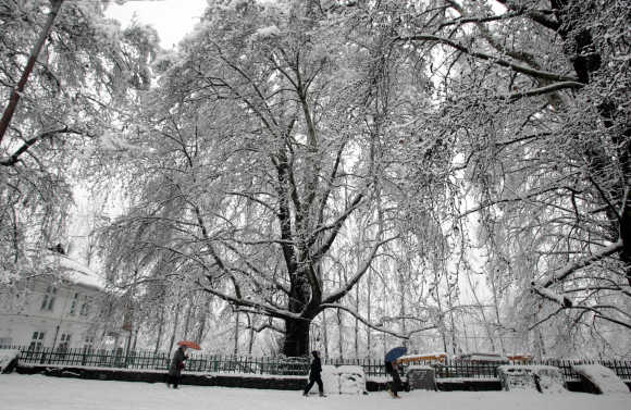 People walk after heavy snowfall in Srinagar.