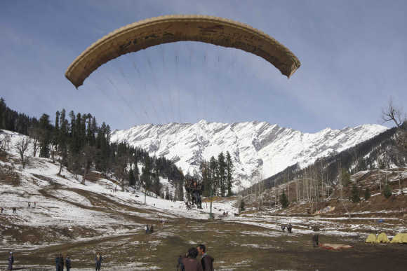 Tourists paraglide after fresh snowfall in Solang Nallah.