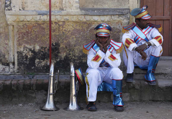 Musicians rest as they wait to take part in a parade during the Kumbh Mela in Haridwar.