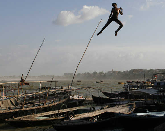 A boy jumps off a promenade into Ganga in Varanasi.