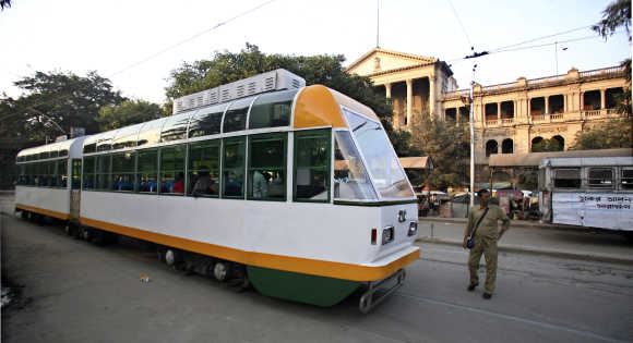 A conductor stands beside a tram in Kolkata.