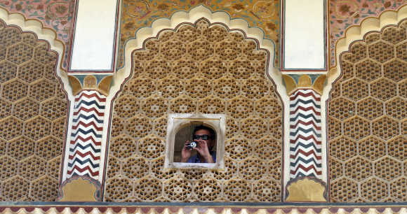 A tourist takes pictures through a window of the Amber Fort in Jaipur.
