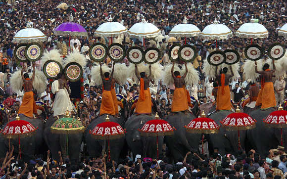 People attend a procession of decorated elephants at Trichur district.