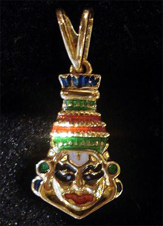 A gold pendant shows Kathakali, a traditional dance form in Kerala.
