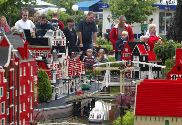 Tourists in the Legoland amusement park in Billund look at a model of Amsterdam made of Lego bricks.