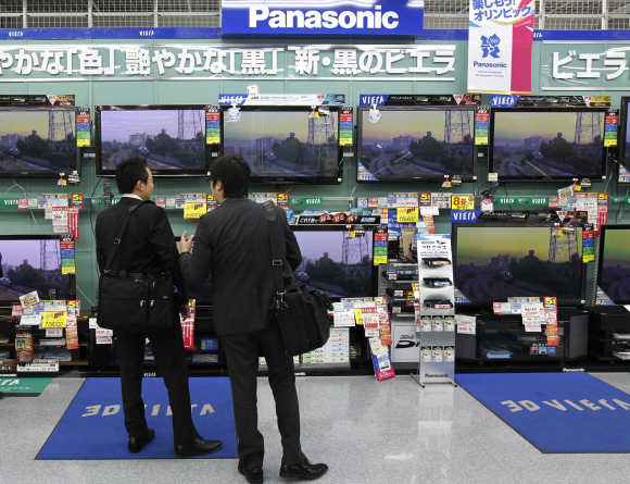 Men look at Panasonic's TV sets at an electronic shop in Tokyo.