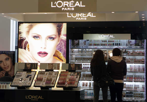 Customers look at LOreal cosmetics in the shop in Riga, Latvia.