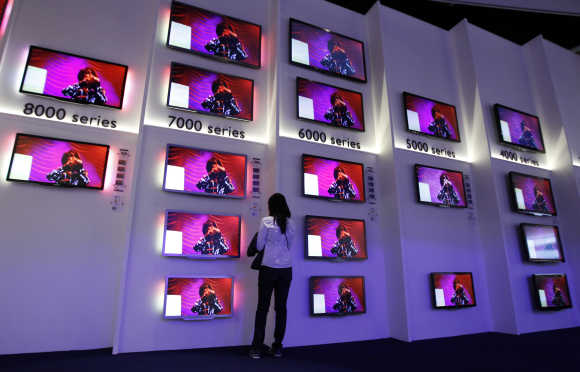 A woman looks at flat screen TV sets in Philips pavilion in Berlin.
