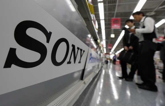 A Sony logo is seen as customers look at digital cameras at an electronic shop in Tokyo.