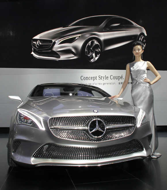 A model stands next to a Mercedes-Benz Concept Style Coupe at Auto China 2012 in Beijing.