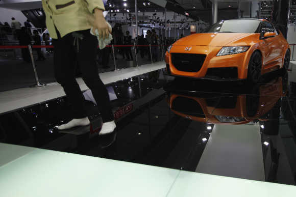 A worker walks past a Honda Motor Co's CR-Z hybrid sports car in Guangzhou, China.