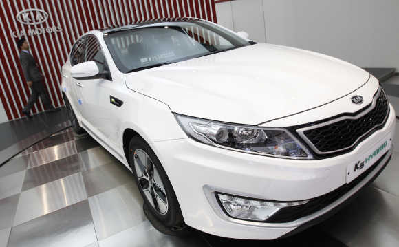 An employee walks past a K5 Hybrid car at a Kia Motors dealership in Seoul.