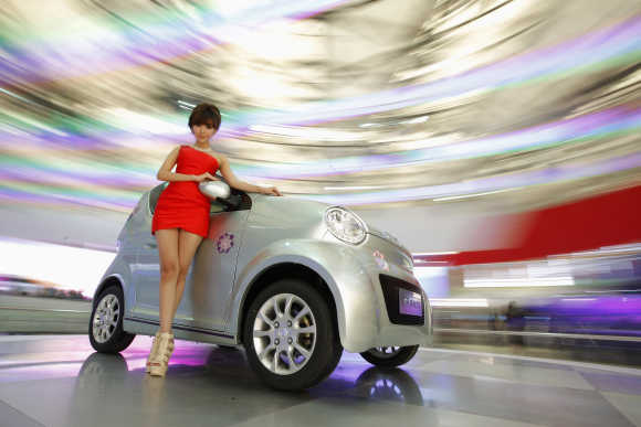 A model poses next to the Dongfeng EJ02 during the opening day of the Shanghai Auto Show.