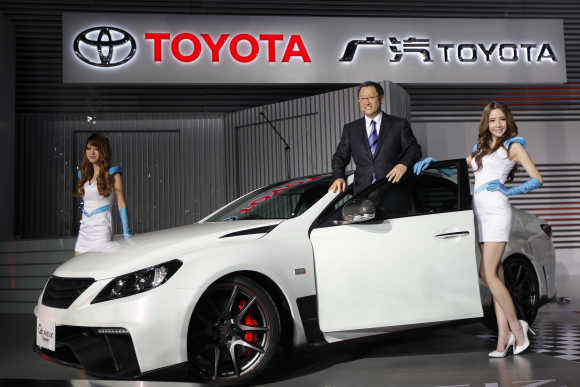 Akio Toyoda, President and CEO of Toyota Motor, poses with models at Toyota G's Reiz concept car during the Shanghai Auto Show.