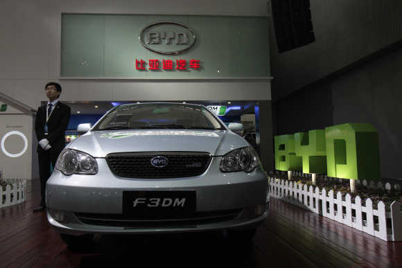 An employee stands near a F3DM, a hybrid car by Chinese automaker BYD Auto, at the Guangzhou Autoshow.