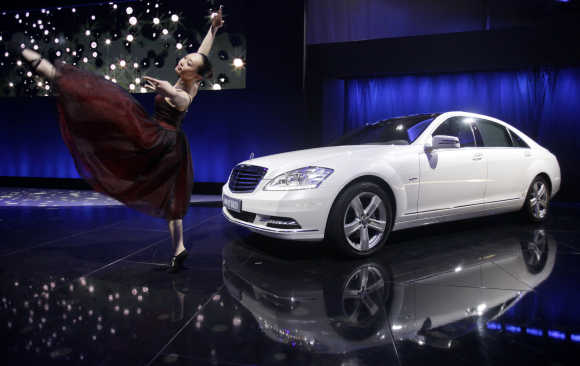 A ballet dancer performs next to Mercedes-Benz S400 Hybrid car in Beijing.