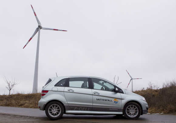 A Mercedes hydrogen-powered car drives near wind turbi