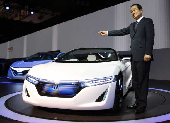 Honda Motor Co President Takanobu Ito poses next to the company's next-generation EV sports car EV-Ster and next-generation plug-in hybrid vehicle AC-X during a news conference at the 42nd Tokyo Motor Show in Tokyo.