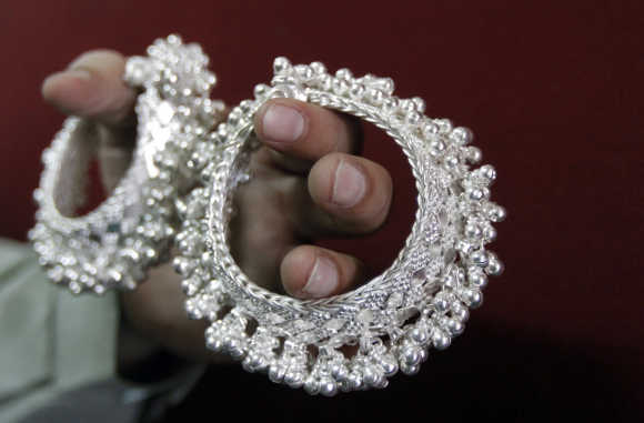 A trader displays silver ornaments inside his shop in Ahmedabad.