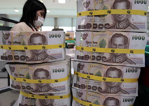 A bank employee counts Thai baht notes at Kasikornbank in Bangkok.