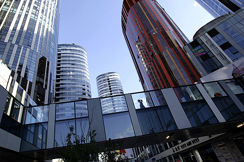 A woman walks between buildings at Sanlitun SOHO residential and commercial complex in Beijing.