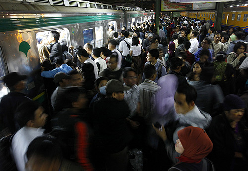 Passengers jostle to enter into a commuter train heading to their homes after work at the Tanah Abang train station in Jakarta.